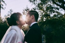 Australian and asian wedding couple kiss under the sunset