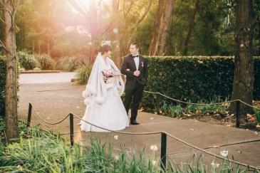 Beautiful australian and asian wedding couple walk at auburn botanic gardens