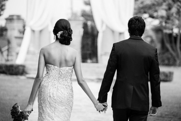 Black and white photo of indian couple holding hands