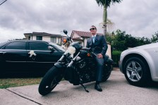 groomsman poses on harley davidson during wedding
