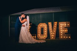 bride and groom kiss in front of large love letters