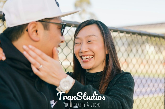 becky holds merven's face on engagement photoshoot at waitara tennis courts