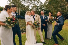 newlywed bride and groom kissing at wedding ceremony with bridal party