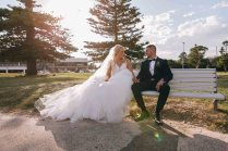 Australian bride and arabic groom sitting on a bench