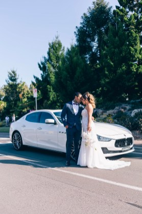 bride and groom in front of maserati wedding car