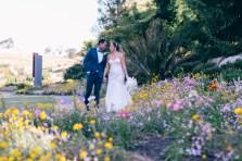 bride and groom walking in field of flowers