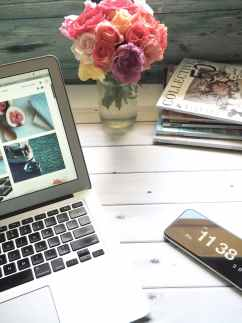 macbook air flower bouquet and magazines on white table