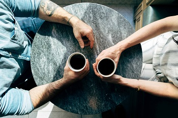 Two arms look at a round table and hold coffee cups