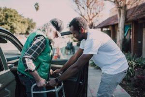 A volunteer helps an elderly man into a car with a walker.
