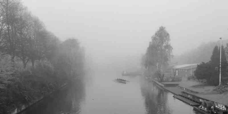 Der Osterbekkanal von einer Brücke fotografiert, er verläuft keilförmig in die Bildmitte. Über dem Wasser ist dicker Nebel, der die Bäume an den Ufern leicht zudeckt.