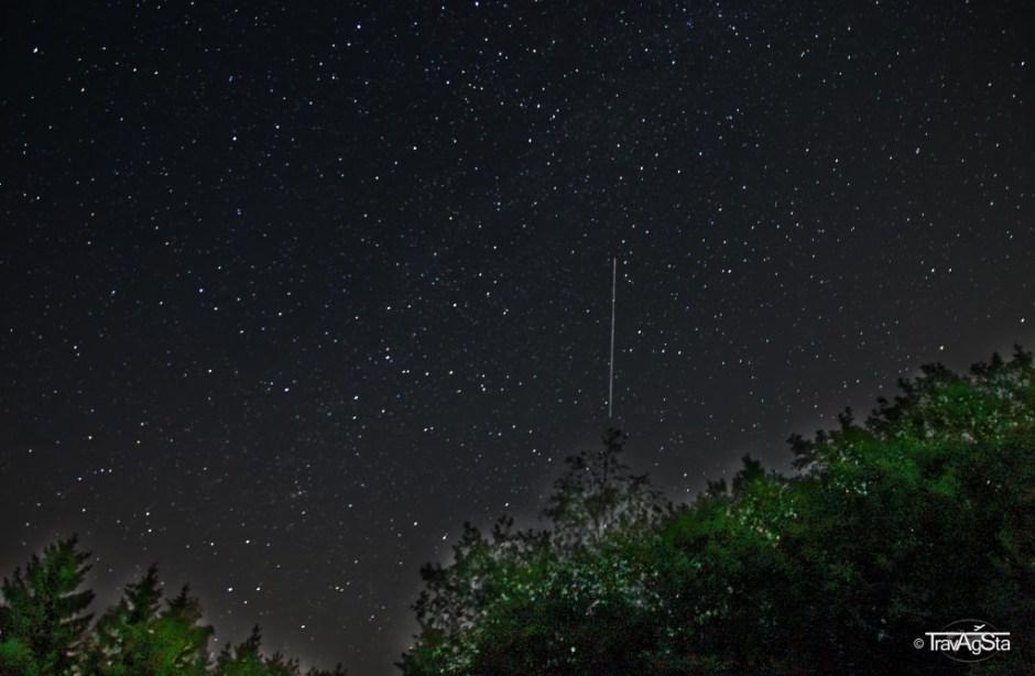 Sternenhimmel mit Sternschnuppe und beleuchtetem Vordergrund