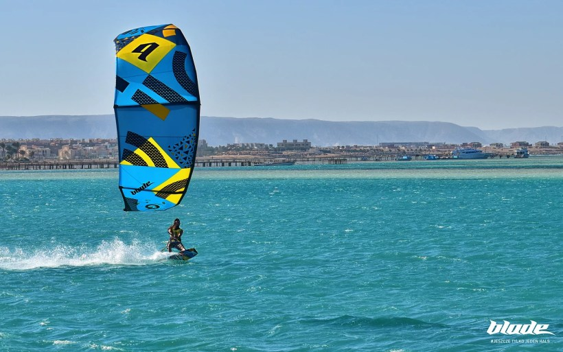 kisurfer riding on a turquoise water with the kite low in Hurghada AMC - one of the best kitesurfing spots in Egypt