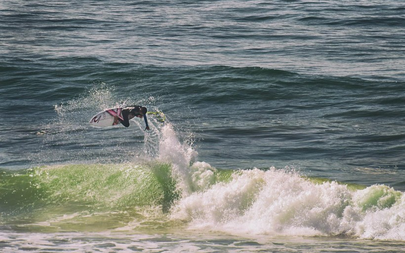 surfer jumping high from the top of the wave in marocco