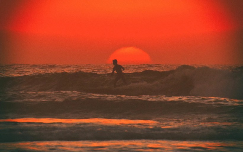 surfer riding the wave with the red sun behind him