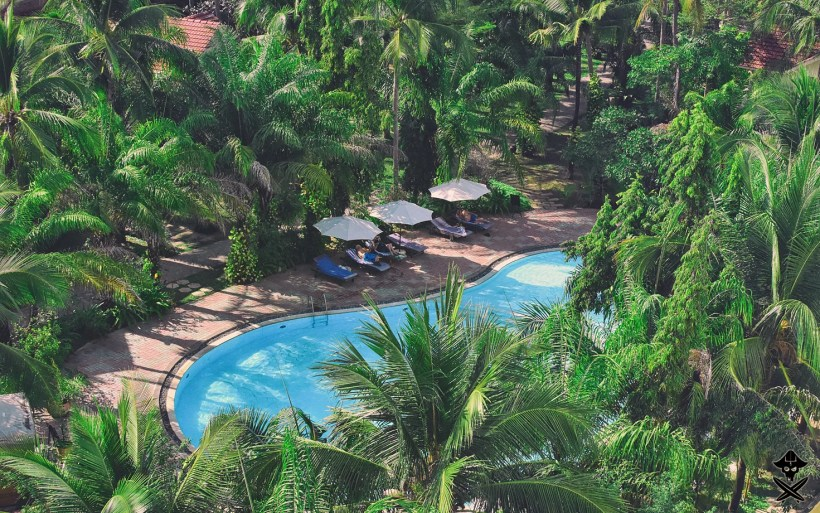 view from the roof top of Unique hotel on the pool and palm trees in Mui Ne Vietnam 2018