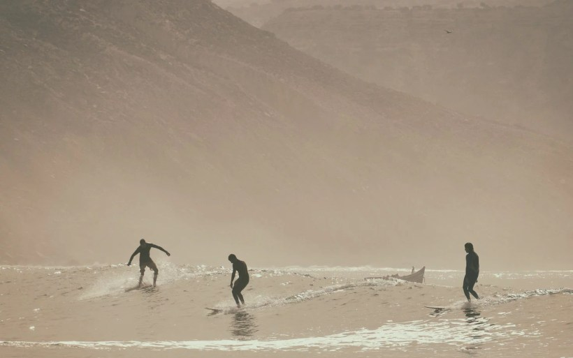 three surfers riding on longboards in marocco insouane the bay