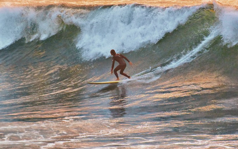 surfer on a long board is preparing to make the bottom turn on big wave that is closing in morocco imsoune cathedral
