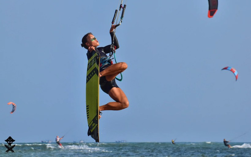 kite girl is doing a transition jump with the nose grab on Phan Rang lagoon in best kitesurfing spot in Vietnam