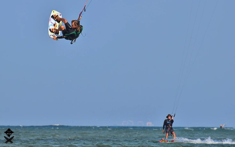kitesurfing instructor Michal Karski i doing big jump with inverted tail grab on Phan Rang lagoon best kite spot in Vietnam