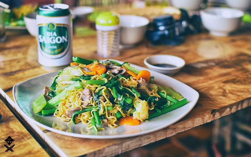 vietnamese food and saigon beer. chicken with pasta and vegetables. Me xao ga. table is wooden