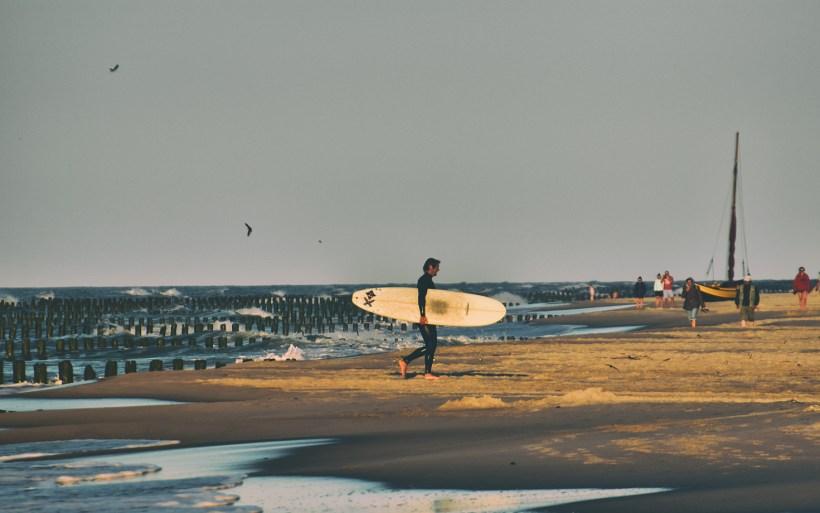 surfer z deską na plaży w Chałupach Bestia