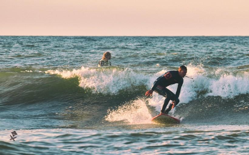 surfer na longboardzie płynie na fali na bałtyku