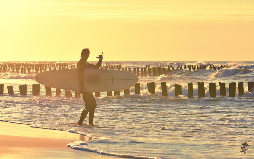 surfer w zachodzącym słońcu pokazuje shaka