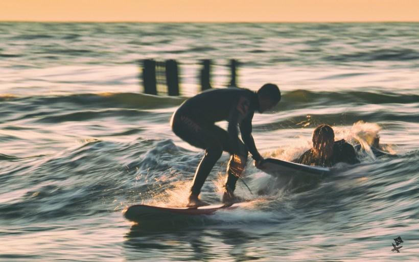 dwóch surferó płynie na jednej fali w chałupach