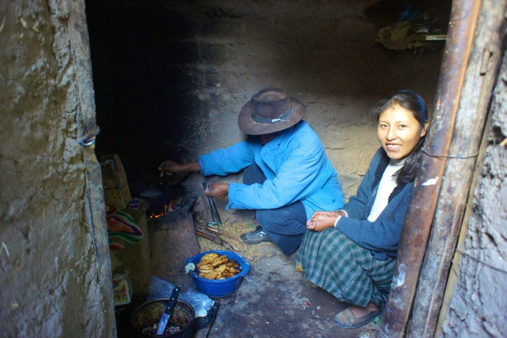 Quechua residents of Amantani Island prepare food over a wood burning stove.