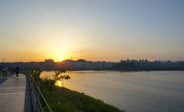 sunset next to the Han River, with a view of Namsan Tower in the distance