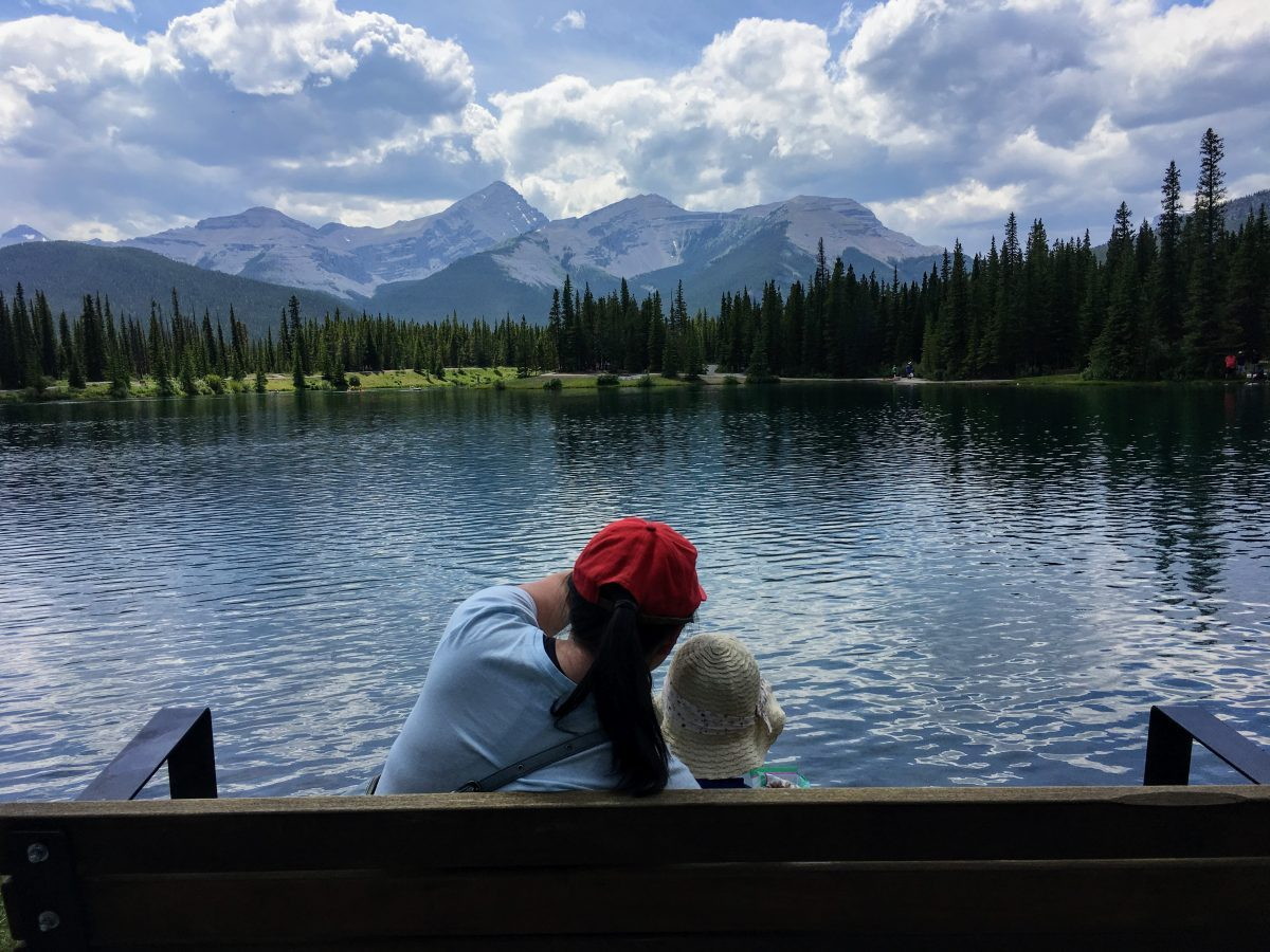 Mom and daughter looking at the forget me not pond in kananaski alberta