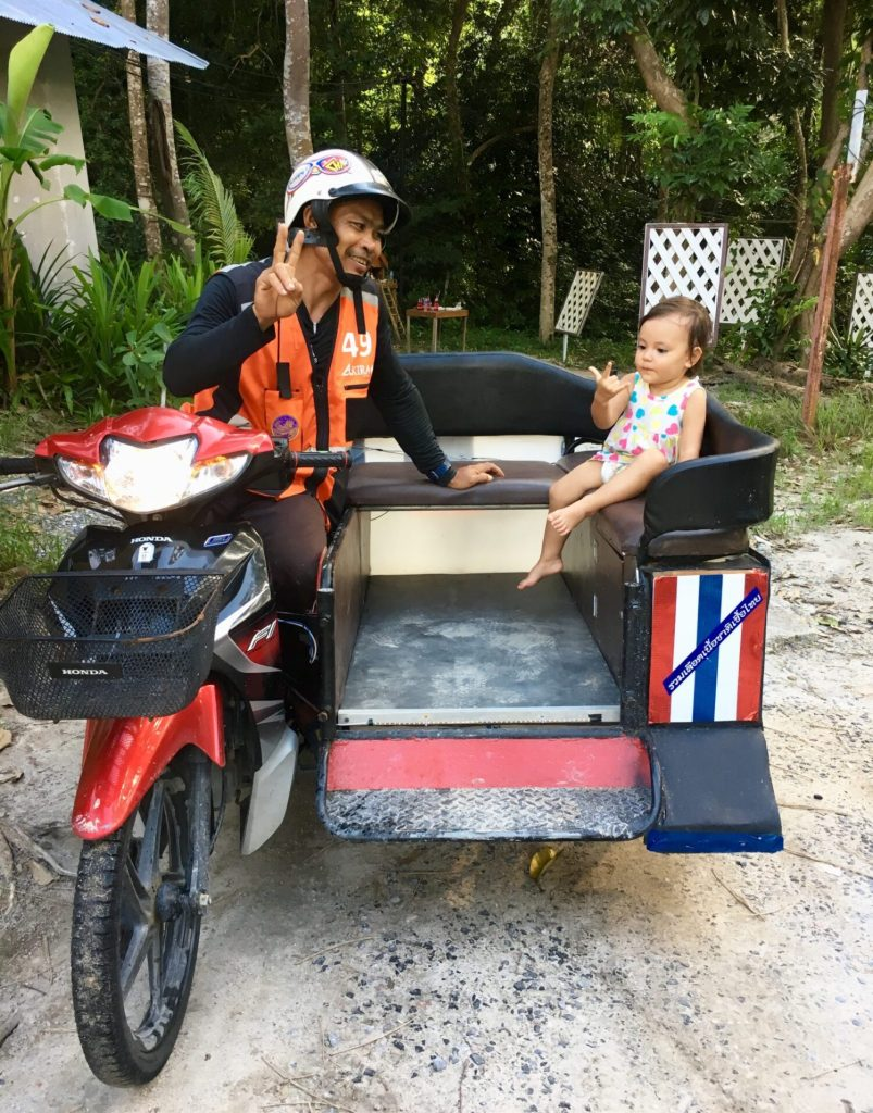 toddler taking a motorcycle taxi to Koh Lipe Sunrise Beach
