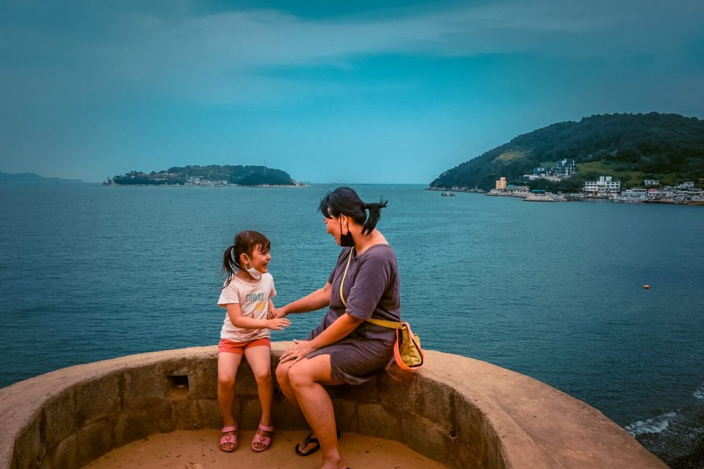 mom and daughter sitting on Maemiseong 메미성 with sea behind them