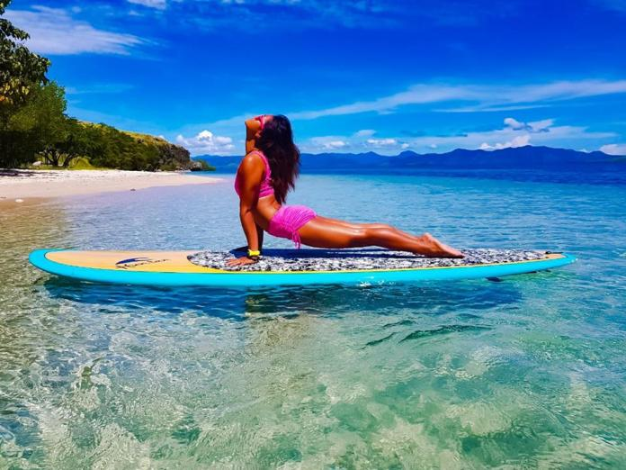SUP yoga comprises all the same asanas as a regular yoga practice – except you're doing it whilst balancing on a paddle board. Image: www.facebook.com/supyogabali