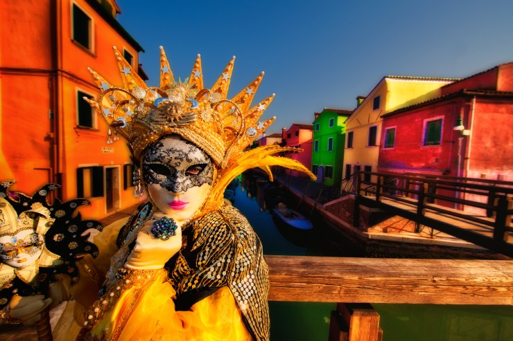 Yellow-costumed model on a bridge on Burano Island during Carnival