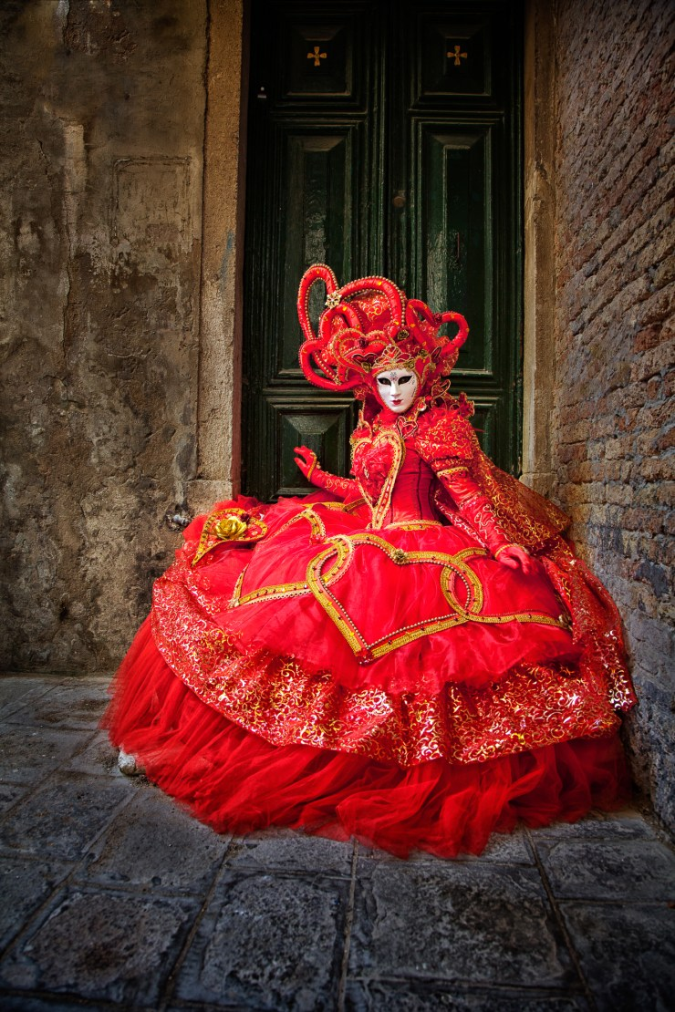 Red costumed model in a Venice doorway during the Carnival celebration