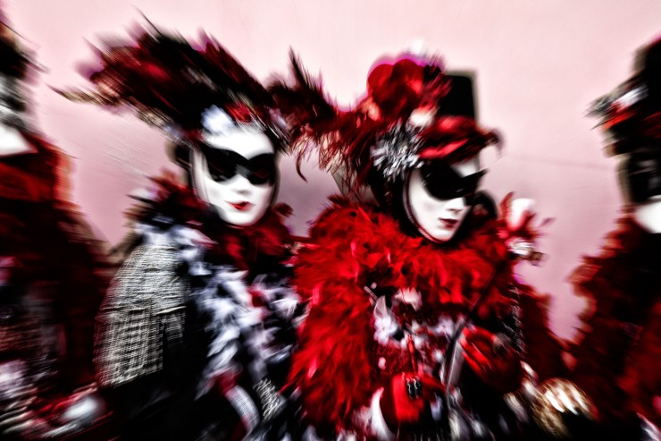 Zoom shot of Venice Carnival models in red, black and white