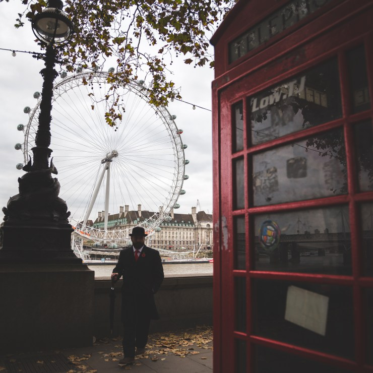 London Eye and a iconic English red telephone box in London. The red telephone box, a telephone kiosk for a public telephone designed by Sir Giles Gilbert Scott, was a familiar sight on the streets of the United Kingdom, Malta, Bermuda and Gibraltar.