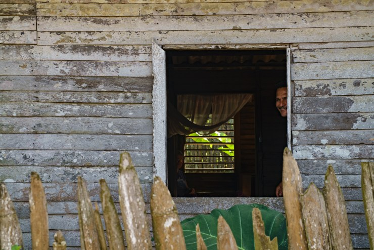 A man smiles out of his window in Baracoa. Photographed with a Tamron 24-70mm f/2.8 at 1/100 and f/5.6.
