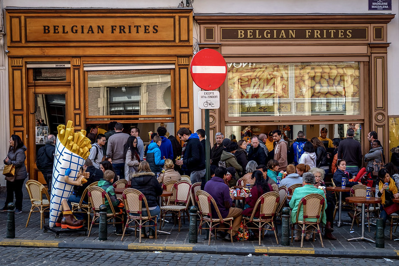 people eating outside in front of restaurant