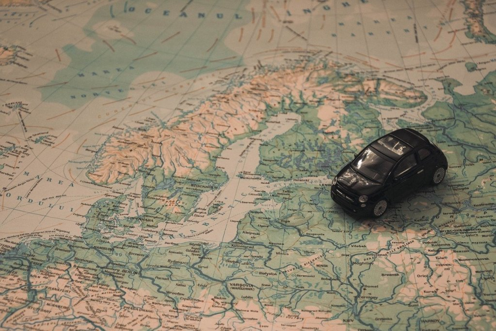 mini car driving over Europe map