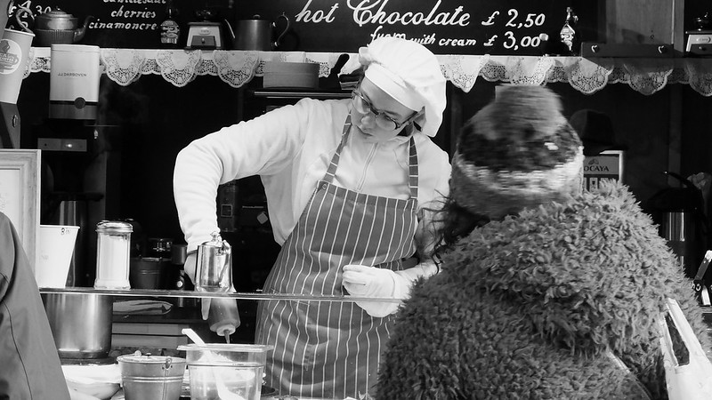 woman serving hot chocolate and cakes