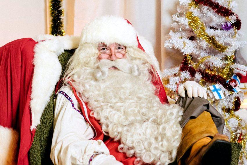 A picture of Santa Claus aittig on his throne