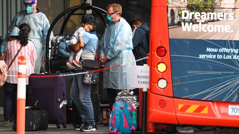 Travelers arrive at a hotel in Melbourne, Australia, to quarantine in December 2020.