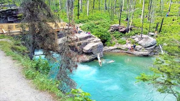 Visitors swimming at St. Mary Falls stream
