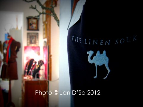 The Linen Souk camel themed apron with the Sue Tyson Jewelry in the background