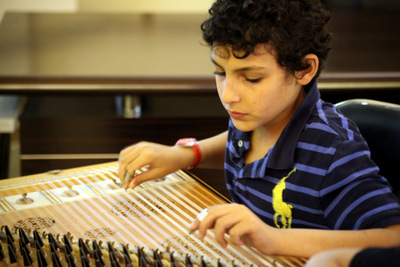 Hamzah Saadah, 10 years old, plays the qanoun. Photos by Hanan Awad ©