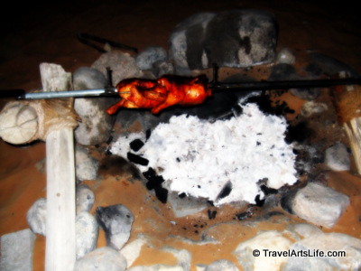 Our dinner roasting on an open-fire spit.