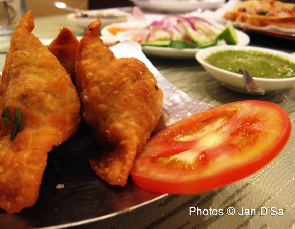 The unforgettable samosas, with the assorted relishes in the background.