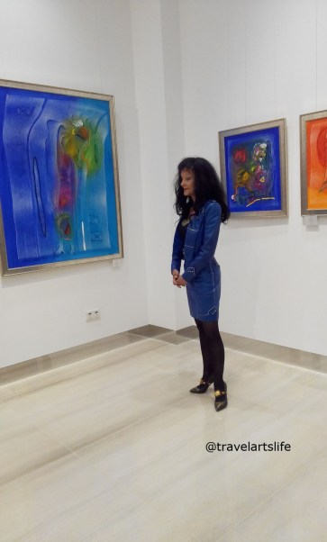The artist posing in front of her colourful works of art